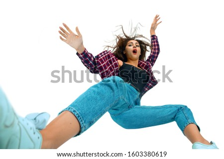 A second before falling. Caucasian young girl falling down in moment with bright emotions and facial expression. Female model in casual clothes. Shocked, scared, screaming. Copyspace for ad. #1603380619