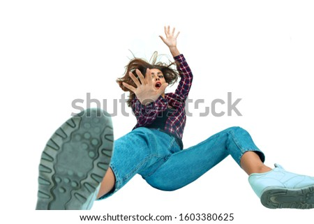 A second before falling. Caucasian young girl falling down in moment with bright emotions and facial expression. Female model in casual clothes. Shocked, scared, screaming. Copyspace for ad. #1603380625