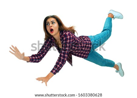 A second before falling. Caucasian young girl falling down in moment with bright emotions and facial expression. Female model in casual clothes. Shocked, scared, screaming. Copyspace for ad. #1603380628