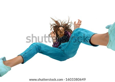 A second before falling. Caucasian young girl falling down in moment with bright emotions and facial expression. Female model in casual clothes. Shocked, scared, screaming. Copyspace for ad. #1603380649