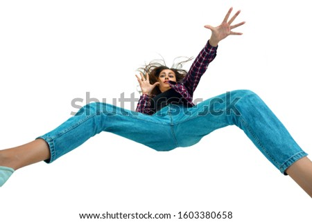 A second before falling. Caucasian young girl falling down in moment with bright emotions and facial expression. Female model in casual clothes. Shocked, scared, screaming. Copyspace for ad. #1603380658