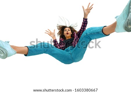 A second before falling. Caucasian young girl falling down in moment with bright emotions and facial expression. Female model in casual clothes. Shocked, scared, screaming. Copyspace for ad. #1603380667