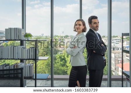 Men and women in the airs, business people standing, arms crossed, looking back and looking at the camera. The dress looks good and is reliable. With a transparent glass backdrop Can see the scenery #1603383739