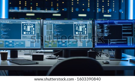 Shot of Multiple Personal Computer Monitors Showing Coding Language Program with System Monitoring Interface. In the Background Data Center with Server Racks. Royalty-Free Stock Photo #1603390840