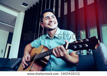 Cheerful guitarist. Cheerful handsome young man playing guitar and smiling while sitting at room, process color #1603418152