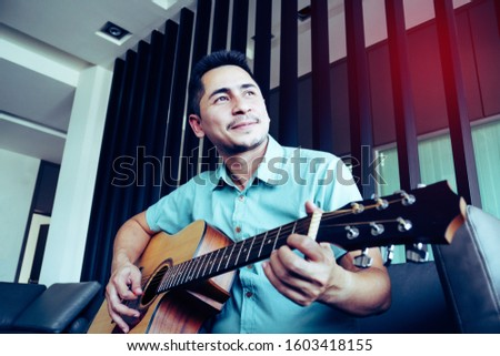 Cheerful guitarist. Cheerful handsome young man playing guitar and smiling while sitting at room, process color #1603418155