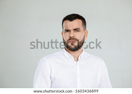 Portrait of young frowned handsome bearded man on gray background. facial expression #1603436899