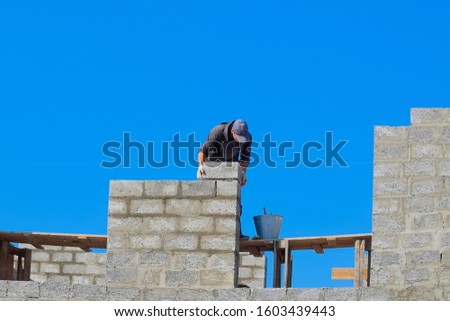 The builder builds the wall of the house from the cinder block. Worker at the construction site #1603439443