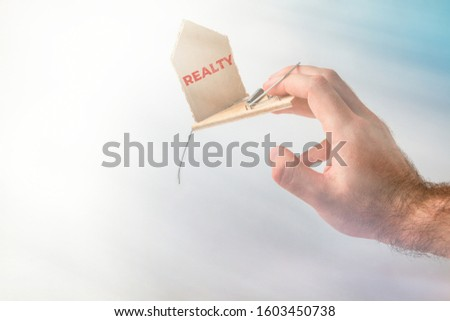 Bank investments and risks. A man's hand was caught in a mousetrap with a schematic cardboard house, with the inscription REALTY. In the background, heaven and light #1603450738