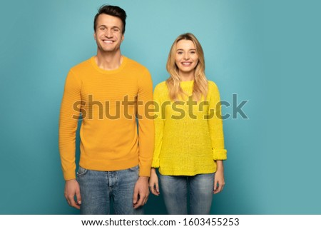 Matching sweaters. Close-up photo of a charming couple, who are posing in yellow sweaters with their arms down, looking in the camera and smiling. #1603455253