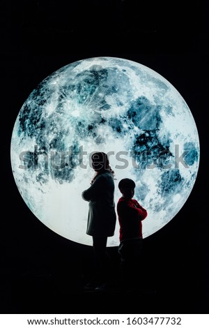 Silhouette picture of grandma and grandson stand on the mountain with A big full moon at night.