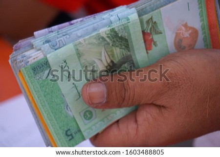 Malaysia money or bank notes stacking. Close up on Malaysia Ringgit money. Calculation to pay debts and daily expenses. Selective focus. #1603488805