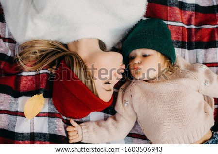 Lovely beautiful family lying face to face and want to kiss. Mother and daughter on picture. Lying on blanket. Wear same jeans and sweaters. Colorful hats. Autumn time