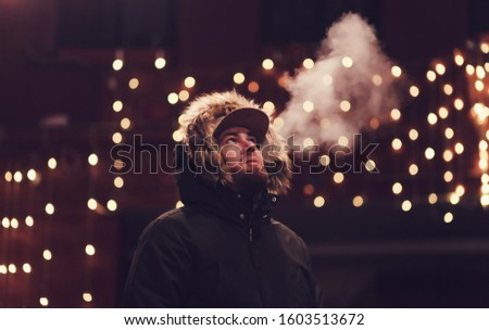 man in a jacket smoking a cigarette against the background of the night city #1603513672