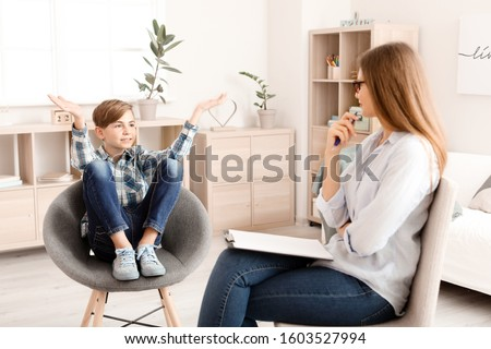 Female psychologist working with boy in office Royalty-Free Stock Photo #1603527994