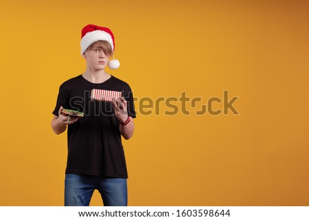 Young guy in a red santa hat holds a gift box in his hands and poses on a yellow background #1603598644