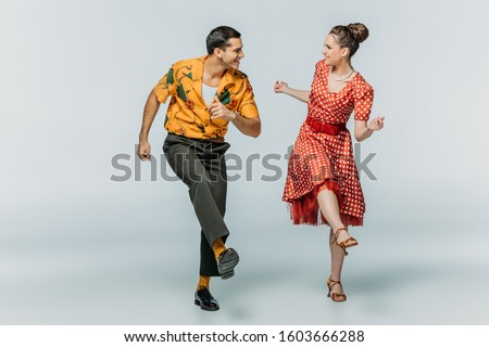 stylish dancers looking at each other while dancing boogie-woogie on grey background Royalty-Free Stock Photo #1603666288