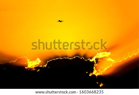 Plane in sunset sky above clouds. Sunset plane silhouette in orange sky. Sunset plane silhouette. Plane in sunset orange sky #1603668235