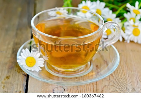 Herbal tea in a glass cup, fresh chamomile flowers on a background of wooden boards #160367462