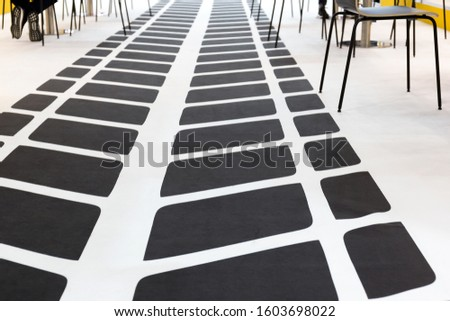 An abstract graphic pattern simulates the footprint of a car's tire tread. Gray stripes on a white background on the office floor.