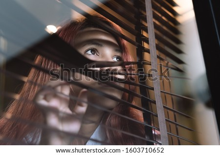 Asian woman looking through window blinds spying on neighbours - Young lonely millennial woman peeping through glass observing gossip and action outdoors - introvert, privacy and intrusive concepts #1603710652
