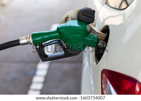 close up nozzle fuel fill oil into car tank at pump gas station #1603734007