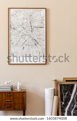 Modern scandinavian living room interior with mock up poster frame, design retro commode, maps, lamp, books and elegant accessories. Beige wall. Japandi. Template. Stylish home decor.