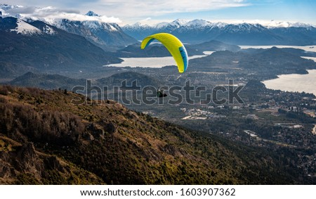 BARILOCHE, ARGENTINA, JUNE 19, 2019: Paragliding over Nahuel Huapi lake and mountains of Bariloche in Argentina, with snowed peaks in the background. Concept of freedom, adventure, flying #1603907362
