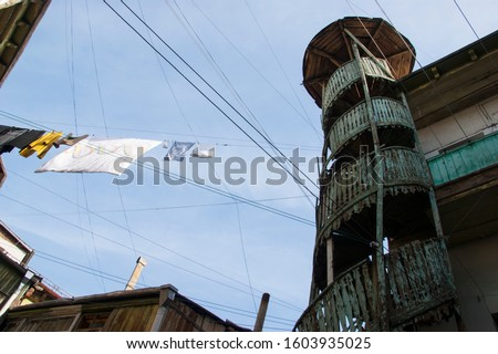 Old Tbilisi. Courtyard in the old town with a broken spiral staircase and lots of clothesline.  #1603935025