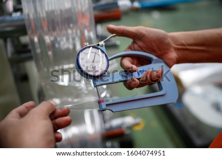 Man's hand is measuring the thickness of the plastic bag type film Polypropylene To check and control the quality Before being used to produce plastic bags. Royalty-Free Stock Photo #1604074951