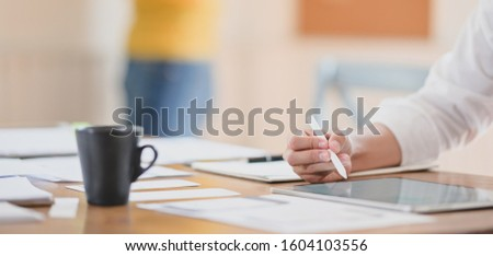 Close-up view of young hard-working ui web designer working on her concept with tablet  #1604103556