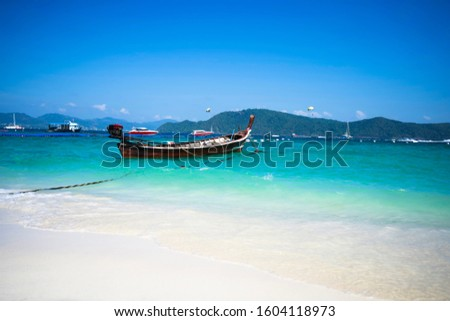 Fishing boat in the blue sea and white sand beach. #1604118973