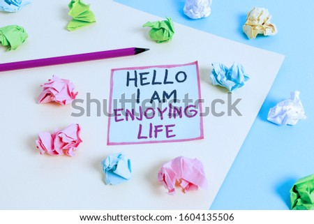 Word writing text Hello I Am Enjoying Life. Business concept for Happy relaxed lifestyle Enjoy simple things Colored crumpled papers empty reminder blue yellow background clothespin. #1604135506