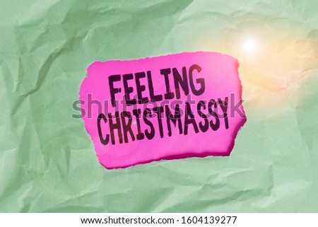 Word writing text Feeling Christmassy. Business concept for Resembling or having feelings of Christmas festivity Green crumpled ripped colored paper sheet centre torn colorful background. #1604139277