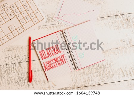 Conceptual hand writing showing Bilateral Agreement. Business photo showcasing Legal obligations to nonbinding agreements of principle Papercraft desk square spiral notebook office study supplies. #1604139748