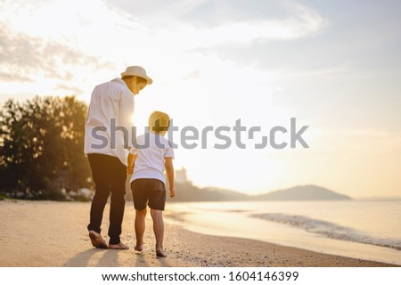 Family, travel, beach, relax, lifestyle, holiday concept. Father and his son who enjoy a picnic and sea bathing at the beach on sunset in holiday.  #1604146399