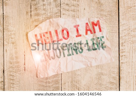 Text sign showing Hello I Am Enjoying Life. Conceptual photo Happy relaxed lifestyle Enjoy simple things Crumpled torn paper half broken placed above classic wooden background. #1604146546