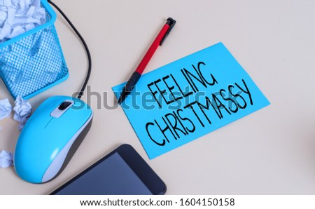 Conceptual hand writing showing Feeling Christmassy. Business photo text Resembling or having feelings of Christmas festivity crumpled paper in bin placed next to modern gadget and stationary. #1604150158