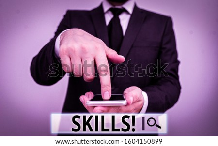 Text sign showing Skills. Conceptual photo ability do something very well by nature Male human wear formal work suit hold smart hi tech smartphone use one hand. #1604150899