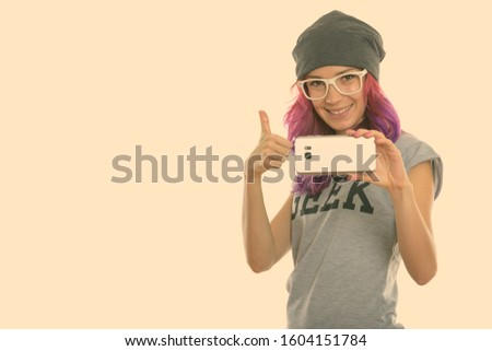 Studio shot of happy geek girl smiling while taking picture with mobile phone and giving thumb up