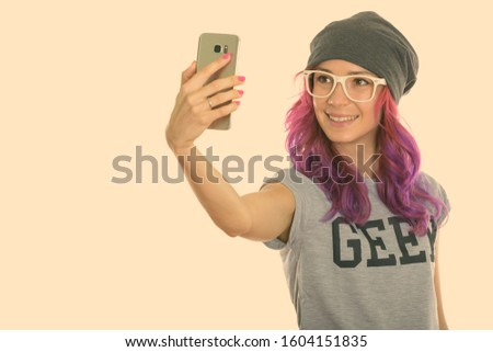 Studio shot of happy geek girl smiling while taking selfie picture with mobile phone