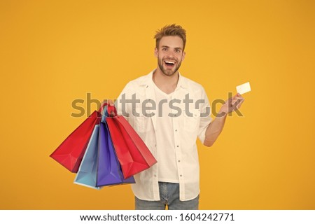 Big discount. Great choices great purchases. Happy man holding purchases in paper bags. Cheerful client customer consumer smiling with fashion purchases. Impulse purchases. Consumerism concept. #1604242771