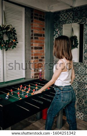 Table games. A happy brunette girl plays table football at home in a cozy atmosphere. #1604251342