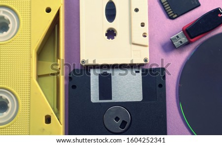 Evolution of memory storage devices, from VHS Tape and Audio Cassette, Film, Floppy disk to USB flash stick and SD memory card. Purple retro background