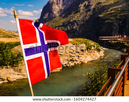 Trollstigen mountain road landscape in Norway, Europe. Norwegian flag waving and many tourists people on viewing platform in background. National tourist route. #1604274427