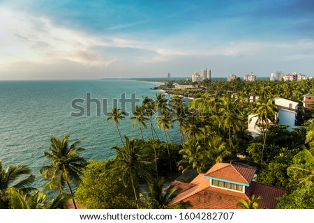 Kerala Tourism concept image Beautiful Beach scenery shot from Kannur Lighthouse, Coconut trees and colorful beach with cloudy sky, best place to visit in Kerala #1604282707