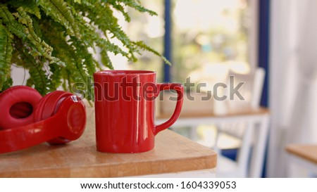 Red coffee cup placed on a wooden table There are blank spaces to fill in the blanks for the product. #1604339053