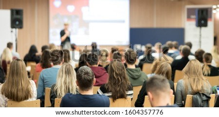 Business and entrepreneurship symposium. Female speaker giving a talk at business meeting. Audience in conference hall. Rear view of unrecognized participant in audience. #1604357776