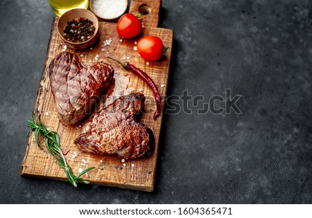 two grilled beef steaks in the form of a heart with spices for Valentine's day on a stone background with copy space for your text. dinner concept for two for Valentine's Day celebration #1604365471