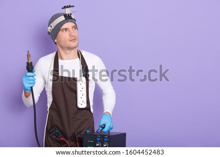 Technician being ready to solder something, attractive male wears white casual shirt, cap and brown apron, holds soldering iron, posing isolated over purple background, looking aside, looks pensive. #1604452483